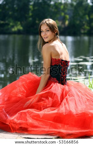 Smiling  beautiful  woman in a red dress sitting near river - stock photo