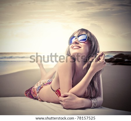 Smiling beautiful woman in bikini lying on a beach - stock photo