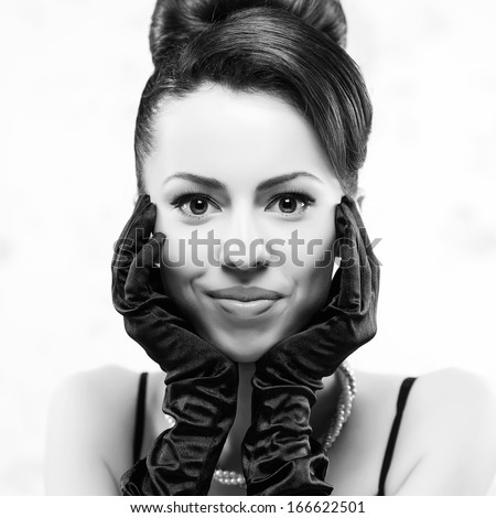Smiling beautiful woman in black gloves with luxurious necklace and great hairdo. Jewelry and Beauty. Vintage (Hollywood, retro) style. Classic old movie star. Close-up. Black and white studio shot - stock photo