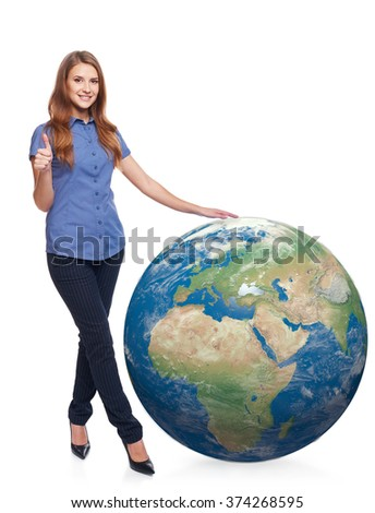 Smiling beautiful woman in full length standing with earth globe, Africa and Europe in front, and gesturing thumb up, over white background