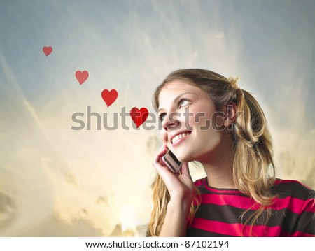 Smiling beautiful woman in love talking on the mobile phone - stock photo