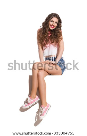 Smiling beautiful woman in pink top, jeans shorts and pink sneakers sitting on the top of white banner. Full length studio shot isolated on white.