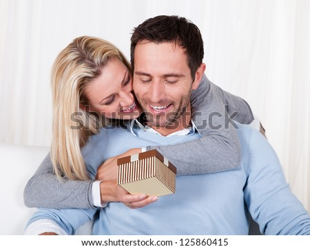Smiling beautiful woman leaning over her husband's shoulder giving him a surprise gift - stock photo
