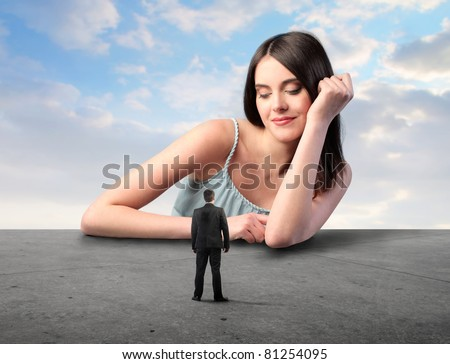 Smiling beautiful woman looking at a tiny businessman - stock photo