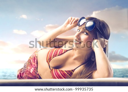 Smiling beautiful woman lying on a beach - stock photo