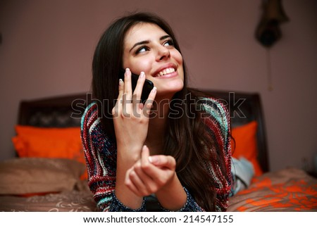 Smiling beautiful woman lying on the bed and talking on the phone - stock photo