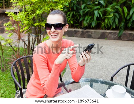 Smiling beautiful woman on her mobile phone outdoors. - stock photo
