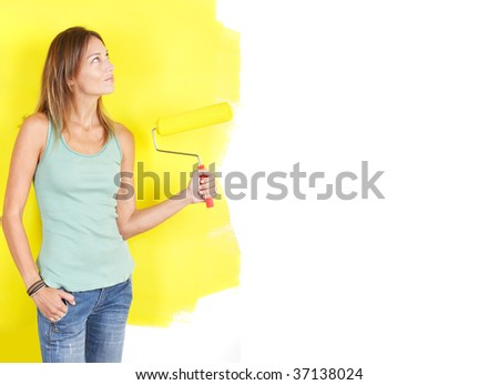 smiling beautiful woman painting interior wall of home. - stock photo