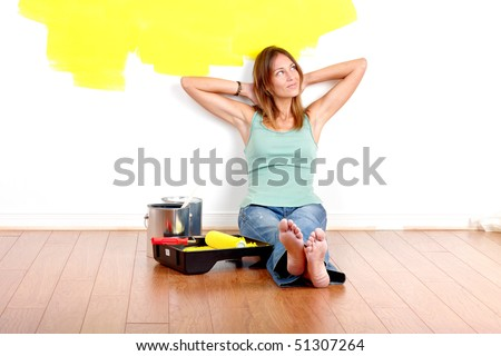 Smiling beautiful woman painting interior wall of home.  Renovation - stock photo