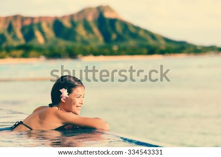 Smiling beautiful woman relaxing in infinity swimming pool. Side view of happy female looking at ocean view on sunny day. Young tourist is enjoying summer vacation against mountain. - stock photo