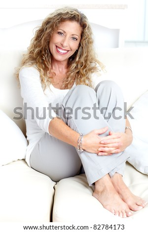 Smiling beautiful woman relaxing on the sofa. - stock photo