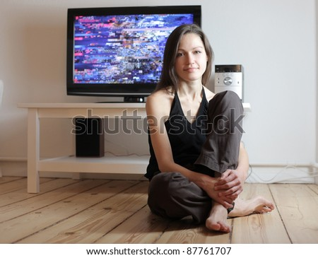 Smiling beautiful woman sitting in front of the television at home