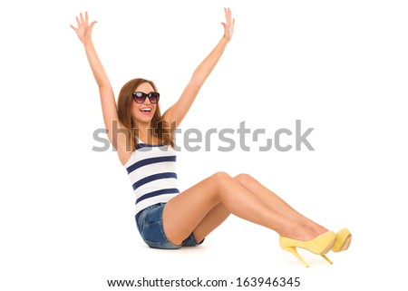 Smiling beautiful woman sitting on the floor and raised hands. Full length studio shot isolated on white. - stock photo