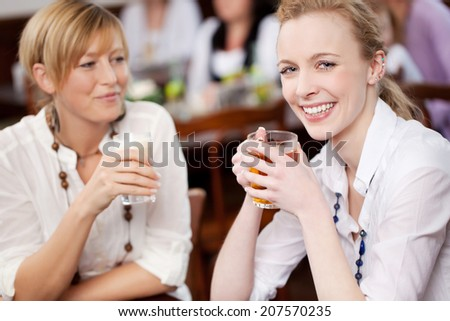 Smiling beautiful woman socialising with a female friend as they sit enjoying refreshments at a restaurant together - stock photo