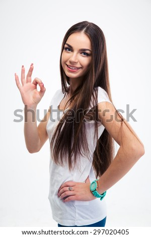 Smiling beautiful woman standing with arms folded isolated on a whtie background. Looking at camera - stock photo