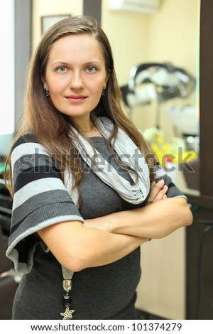Smiling beautiful woman stands near mirror and looks into camera in beauty salon