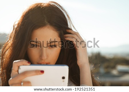 Smiling beautiful woman typing a message on her smartphone. horizontal outdoors shot Toned in warm colors. Copy Space for your text - stock photo