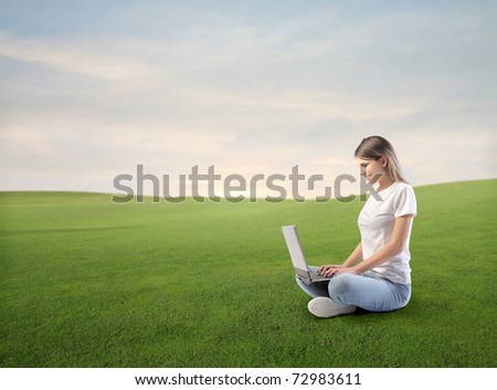 Smiling beautiful woman using a laptop  on a green meadow - stock photo