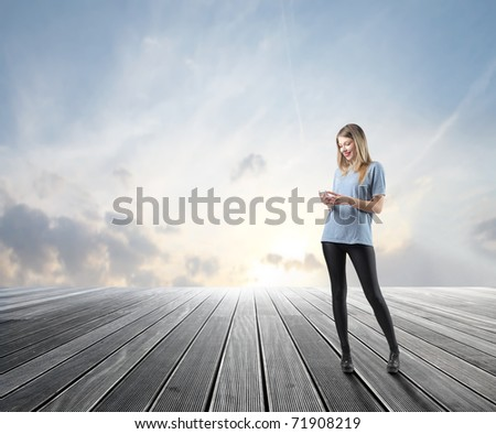 Smiling beautiful woman using a mobile phone on a wooden floor - stock photo