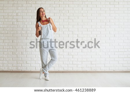 Smiling beautiful woman wear strip overalls, standing and trying on fancy butterfly holding with her hand, white brick wall on background