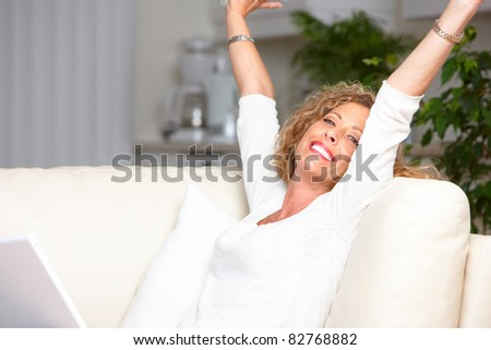 Smiling beautiful woman with laptop. Cosy home. - stock photo