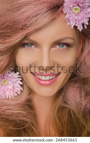 Smiling beautiful woman with pink hair and flowers - stock photo
