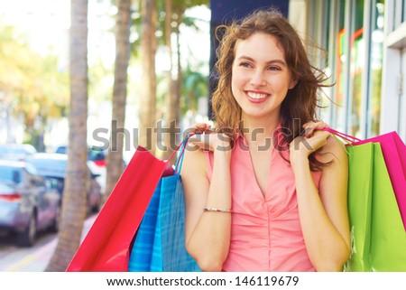 Smiling beautiful woman with shopping bags looking away. Horizontal Shot. - stock photo