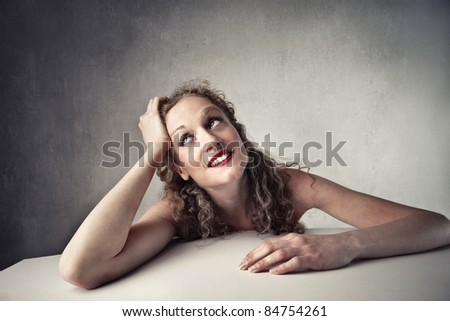 Smiling beautiful woman with thoughtful expression - stock photo