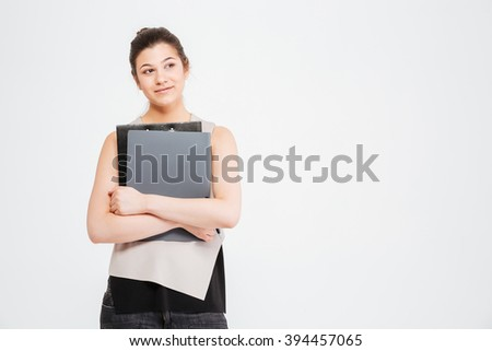 Smiling beautiful young business woman standing and holding folders over white background - stock photo