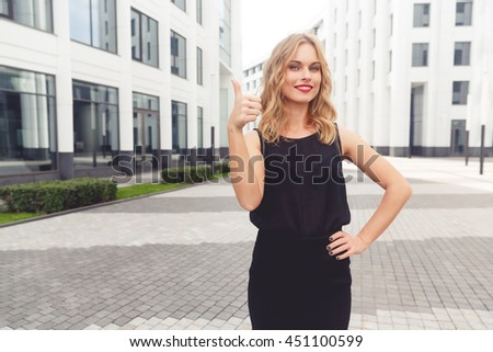 Smiling beautiful young businesswoman showing thumbs up gesture - stock photo