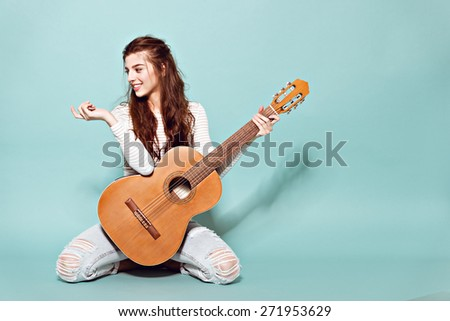 smiling beautiful young girl posing with classic guitar - stock photo