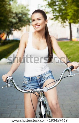 Smiling beautiful young girl standing with her bicycle on the street. City scene. Warm summer day. Inside