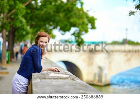 Smiling beautiful young lady on the Seine embankment in Paris - stock photo
