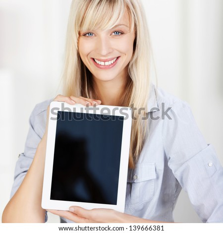 Smiling beautiful young woman holding up a blank tablet with the screen facing the viewer with copyspace for your text