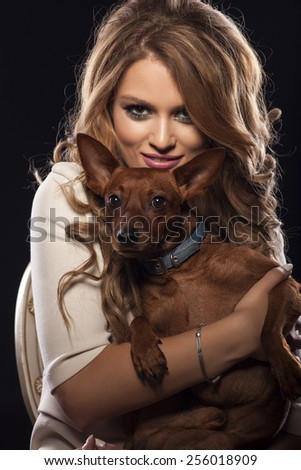 smiling beautiful young woman holds her dog in her arms