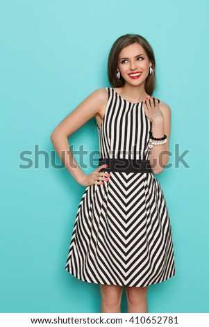 Smiling beautiful young woman in black and white striped dress posing with hands on hip and looking away at copy space. Three quarter length studio shot on teal background. - stock photo