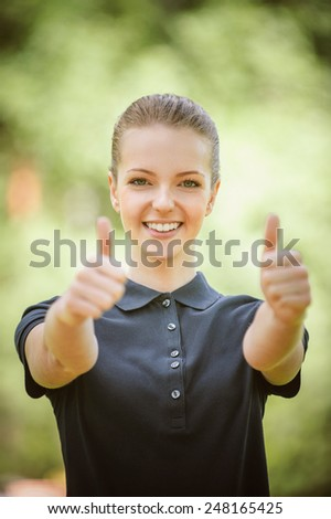 Smiling beautiful young woman in dark blouse lifts thumb upwards, against green of summer park. - stock photo