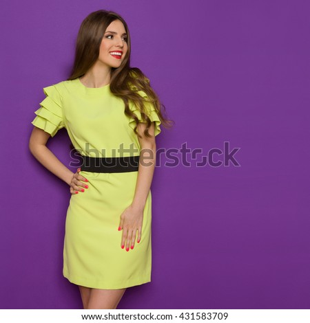Smiling beautiful young woman in lime green dress posing with hand on hip and looking away. Three quarter length studio shot on purple background. - stock photo