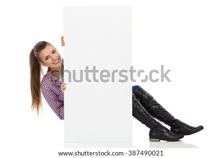 Smiling beautiful young woman in lumberjack shirt and black boots, sitting on floor behind white placard and peeking. Full length studio shot isolated on white. - stock photo