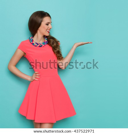 Smiling beautiful young woman in pink mini dress showing product and looking. Three quarter length studio shot on turquoise background. - stock photo