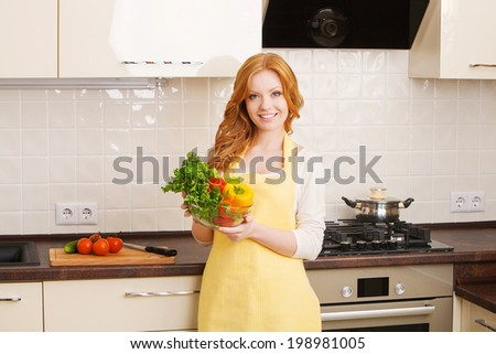 Smiling beautiful young woman in the kitchen with vegetables