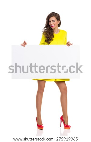 Smiling beautiful young woman in yellow dress and red high heels standing and holding a big white placard. Full length studio shot isolated on white. - stock photo