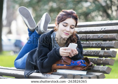 Smiling beautiful young woman looking message on phone, feeling and emotion lifestyle concept. - stock photo