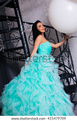 smiling, beautiful young woman lying on a bed in a dress, brooding look - stock photo