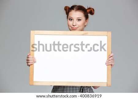 Smiling beautiful young woman showing blank whiteboard over grey background - stock photo