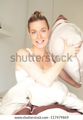 Smiling beautiful young woman sitting in bed taking aim with a pillow during a mock pillow fight