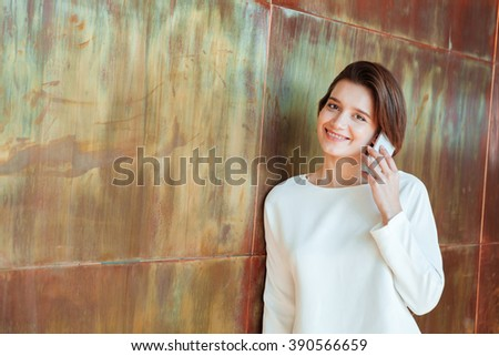 Smiling beautiful young woman standing and talking on mobile phone in office - stock photo