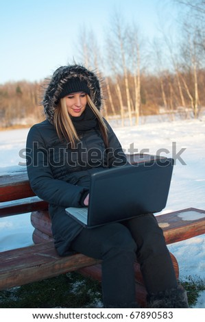 Smiling beautiful young woman watching laptop sitting on a bench in winter surrounded by snow - stock photo