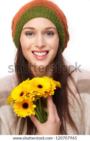 Smiling beautiful young woman wearing a hat and holding yellow flowers. Isolated on white background - stock photo