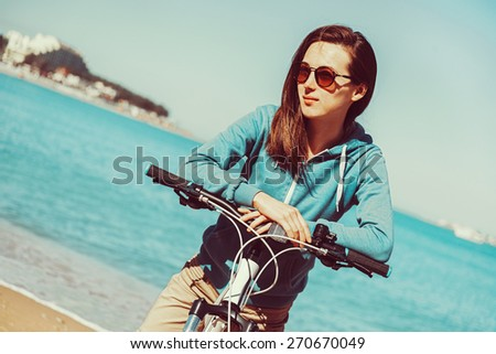 Smiling beautiful young woman with a bicycle on beach in summer - stock photo